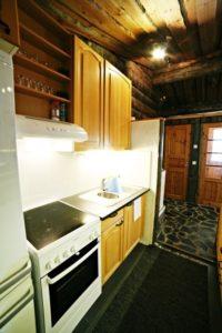 Vuokramökin keittiössä liesi, astianpesukone, jääkaappipakastin